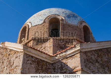 Abandoned church od Saint John (Agios Ioannis) in the country close to Cape Sounion in Greece. View on the exterior of the dome and roof. Bright blue sky.