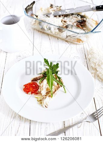 helthy food composition: Seabass in white plate baked in sea salt with arugula leaves and soy sauce. White wood background