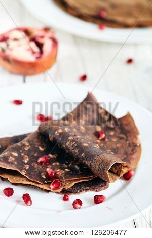Healthy chocolate pancakes without eggs and sugar on white wood table. Pomergranate seed near white plate with crepes and big plate with pancakes on back