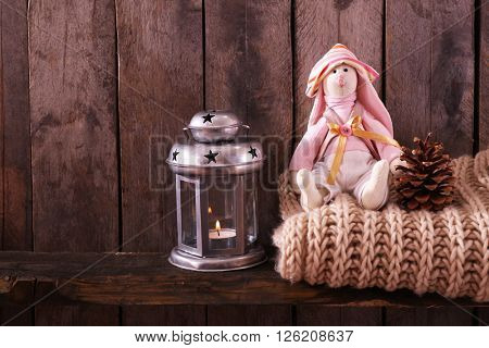 Toy bunny with woolen scarf and lantern on wooden background