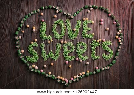 Love sweets inscription with candies on wooden background
