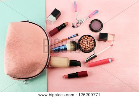 Makeup set with beautician, eyelash curler, brushes and cosmetics on bright background