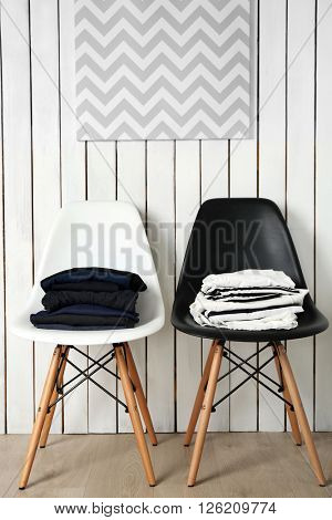 Stack of clothes on black and white chairs over wooden wall background