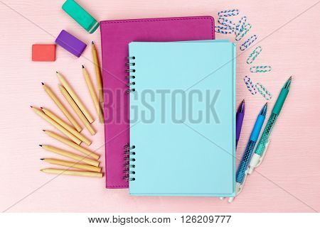 Office set with notebooks, colored pens and pencils on pink background