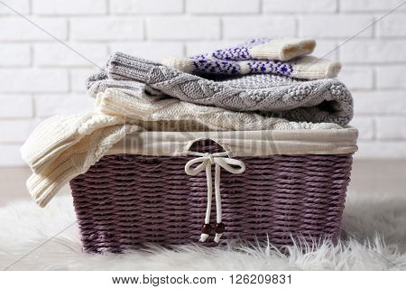 Pile of woolen clothes with basket on white carpet in light interior