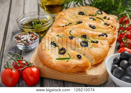 Italian focaccia bread with olives and rosemary on rustic wooden background, selective focus