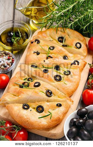 Italian focaccia bread with olives and rosemary on rustic wooden background, top view