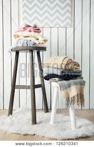 Stacks of woolen clothes on wooden stools in a light interior
