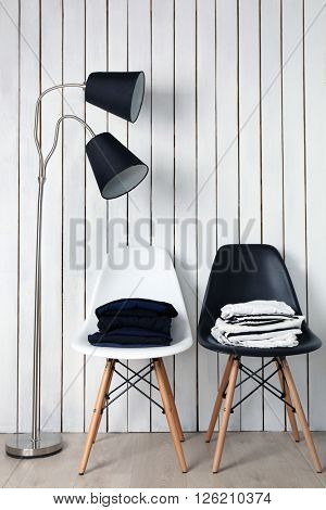 Stack of clothes on black and white chairs with lamp over wooden wall background