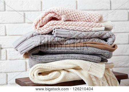 Stack of woolen clothes on wooden stool over white brick wall background
