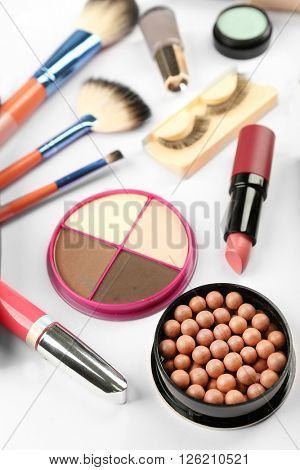 Makeup set with false eyelashes, brushes and cosmetics on white background
