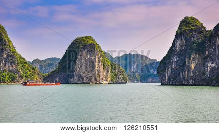 Barge on the background of rocky islands in Halong Bay.