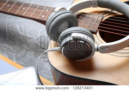 Classical guitar and headphones on grey background, close-up
