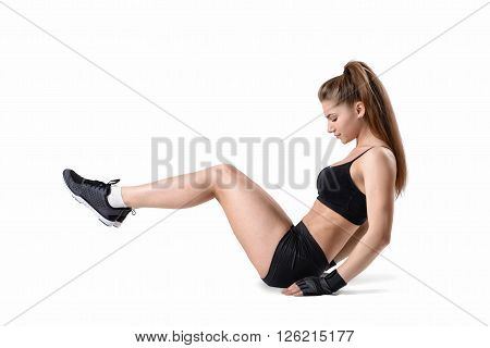 Fitness girl during exercise to strengthen and tone up the entire abdominal wall. Sitting exercise, balanced just behind her sits bones and rock back slightly to lift her feet off.