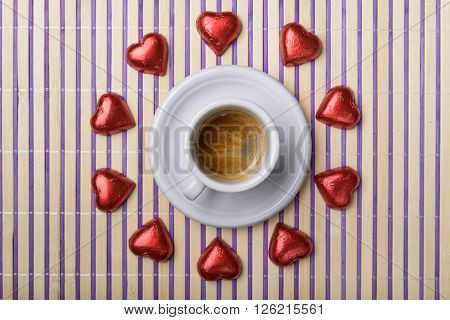 clock made with cup of coffee and red wrapped chocolate heart on placemat