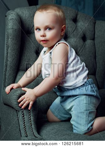 one and a half year old boy in the chair at home