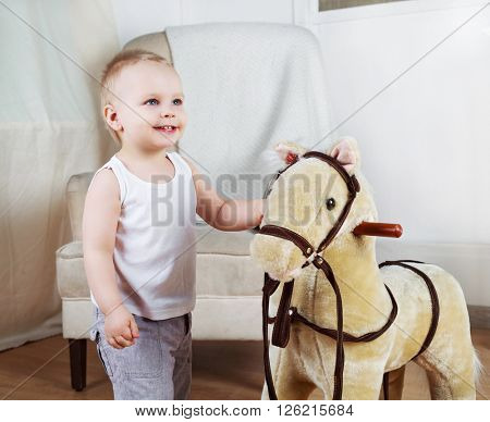 happy boy playing with a toy horse at home
