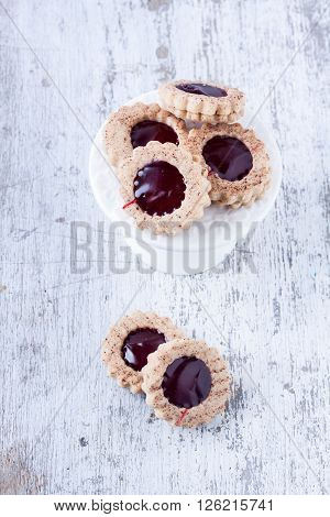 cookies with jam on a white wooden background