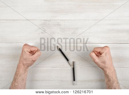 Closeup masculine fists clenched on wooden panel in top view. Anger sign.