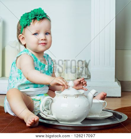 cute one year old girl drinking tea at home