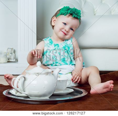 cute one year old baby drinking tea at home