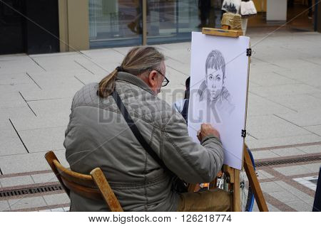 Frankfurt am Main, Hessen, Germany - April 18, 2016: A street artist drawing a picture of a boy. He makes a living by drawing people's face on the street.