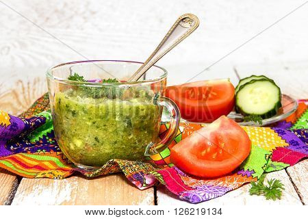 mashed tomatoes and cucumbers in a transparent cup