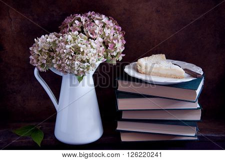 Dried hydrangea flowers in a white jug and pie