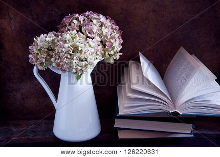 Dried hydrangea flowers in a white jug and books