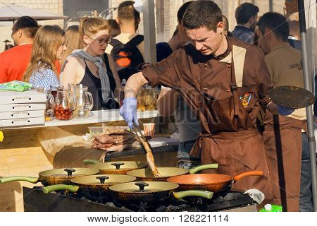 KYIV, UKRAINE - APR 17: Weary cook prepares meat dishes in cast iron pans in outdoor kitchen during Street Food Festival on April 17, 2016. Kiev is the 8th most populous city in Europe.