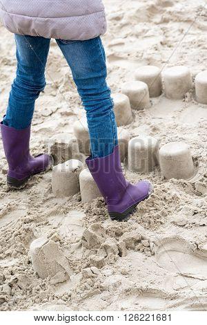 Little girl crushing mud pies on a beach
