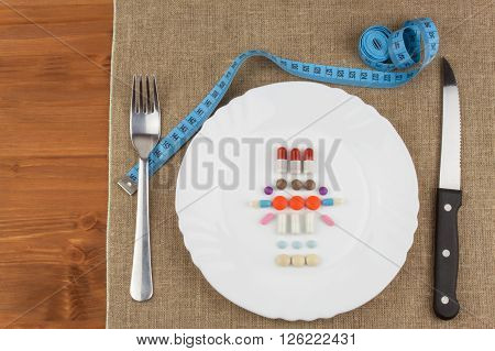 Diet products on a white plate. A plate of food supplements and cutlery. Diet food. Strict diet for athletes. Anabolic steroids in sports training.