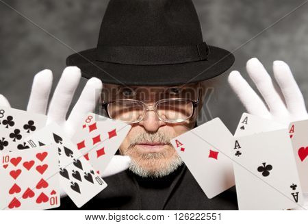 Magician show with playing cards. On grey background