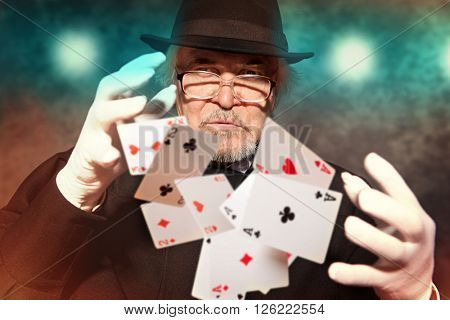 Magician show with playing cards. On color background
