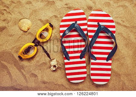 Pair of thongs or flip flops and swimming glasses on beach sand top view of summer holiday vacation accessories on sandy summertime resort coastline.