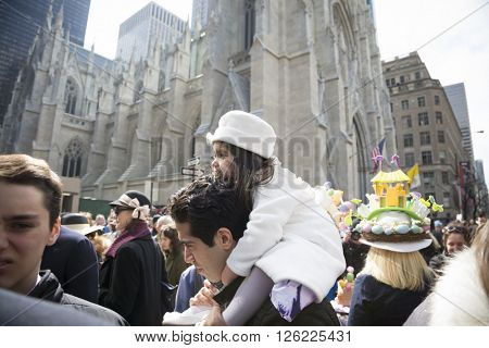 NEW YORK - MAR 27 2016: A young girl wearing a white Easter hat sits on a mans shoulders above the crowd on 5th Ave Easter Sunday at the traditional Easter Bonnet Parade in Manhattan, March 27, 2016.