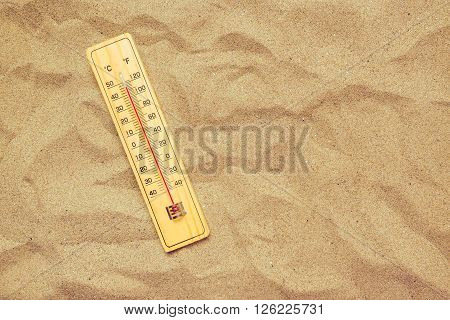 Record high temperatures thermometer with celsius and farenheit scale on warm desert sand.