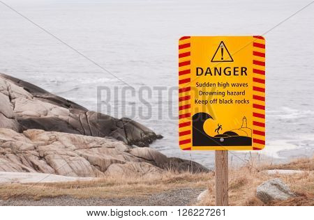 Danger sign warning of drowning hazard from high waves.
