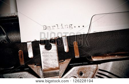 Darling word on white paper typed on old black typewriter