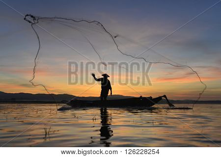 Silhouette Fisherman in action fishing Thailand .