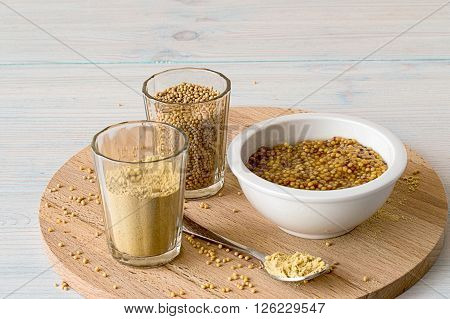 Mustard in white cup, mustard seeds and mustard powder in a glass on a wooden board.