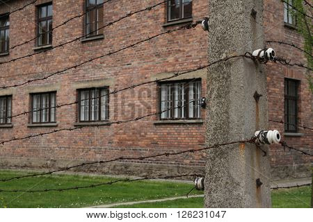 Oswiecim, Poland - May 09, 2015: Electric Fence And Buildings In Former Nazi Concentration Camp Ausc