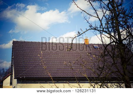 brown roof with chimney and Lightning conductor - blue sky tree