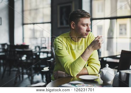 Self-sufficient middle-aged man sitting at a table in a deserted cafe and drinking tea