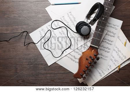 Electric guitar and headphones with musical notes on wooden background