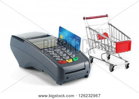 Payment terminal with inserted credit card and supermarket trolley, isolated on white
