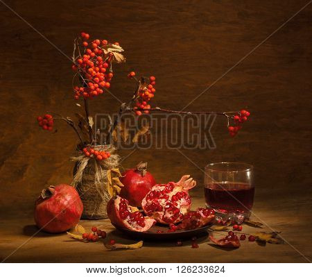 Still life of pomegranate juice and fruits, and rowan berries on a wooden background ** Note: Visible grain at 100%, best at smaller sizes