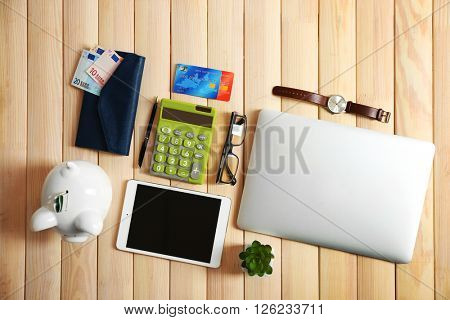 Piggy bank with digital devices, credit cards and other accessories on wooden table, top view