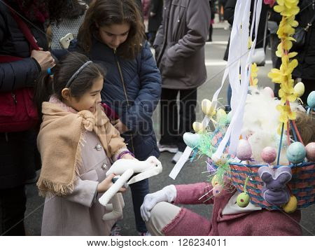 NEW YORK - MAR 27 2016: A young girl holding a white rabbit talks to a woman wearing a basket of eggs on her head on 5th Avenue at the traditional Easter Bonnet Parade in Manhattan on March 27, 2016.