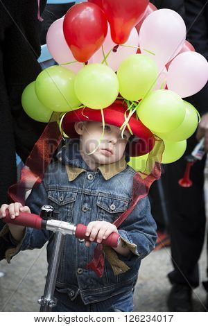 NEW YORK - MAR 27 2016: A young boy on a razor scooter wears an Easter bonnet made of balloons on 5th Avenue Easter Sunday for the traditional Easter Bonnet Parade in Manhattan on March 27, 2016.